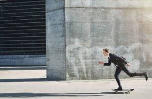 Businessman on a skateboard moving forward fast